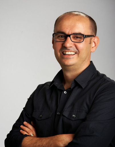 man smiling with his arms crossed and glasses on