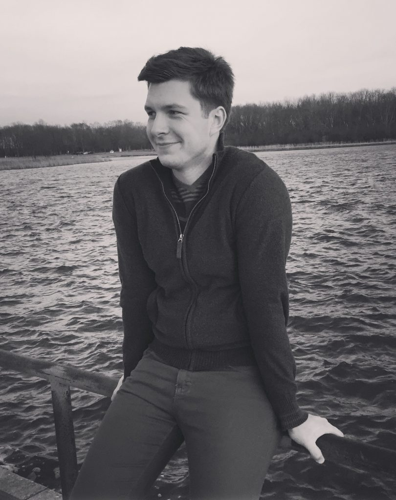 man leaning against a rail at a river smiling