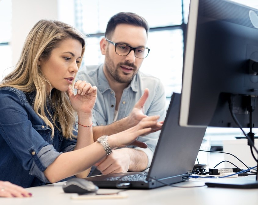 Man and woman discussing over a laptop and next to a desktop computer